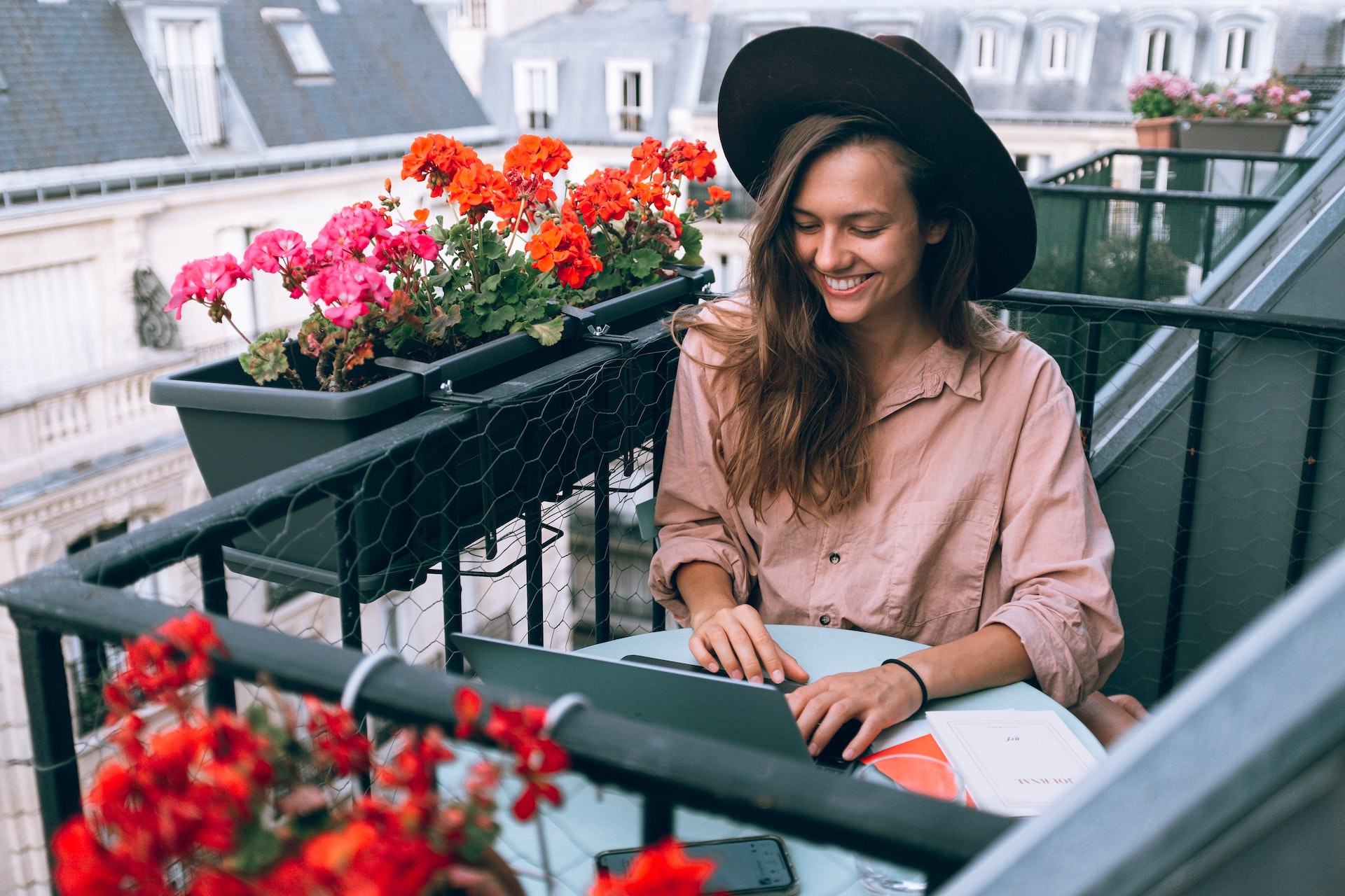 Woman on her terrace, working on her website.