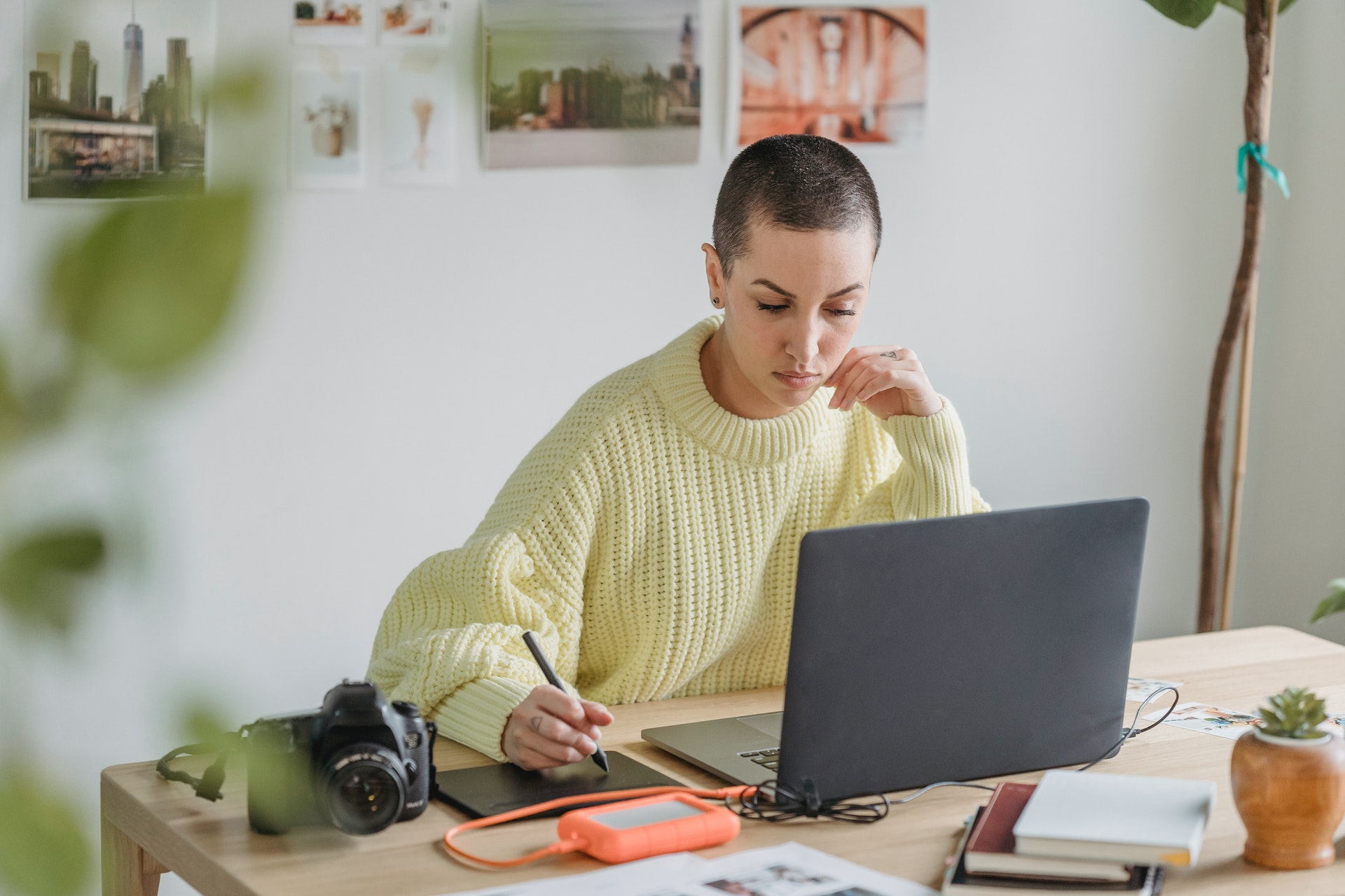 Short-haired woman with light yellow sweater, illustrating with their computer.